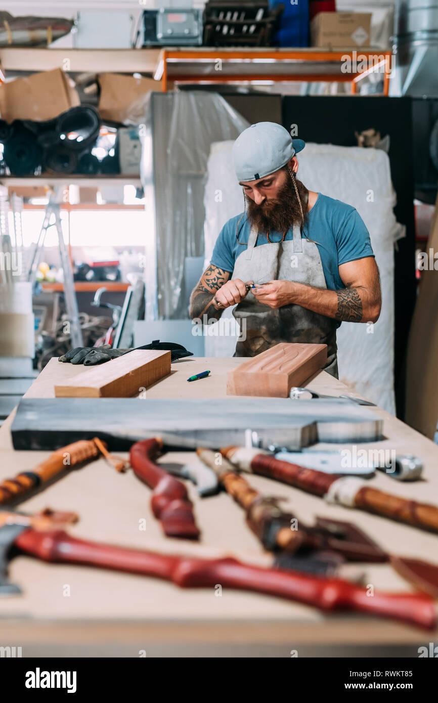 Ax travaillant sur le bois pour manche de hache en atelier Banque D'Images