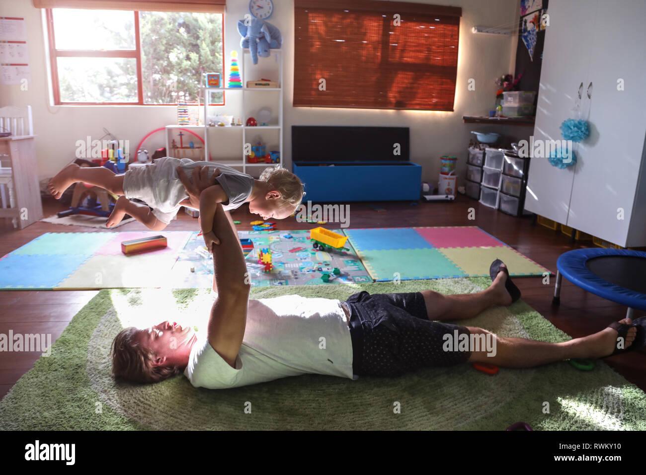 Père lying on floor, levage baby boy dans l'air Banque D'Images