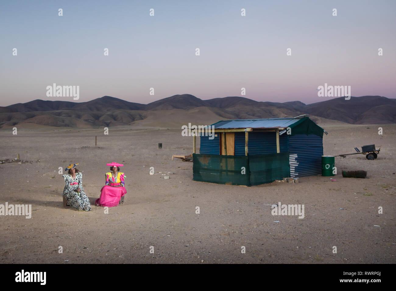 Les femmes Herero s'asseoir à l'extérieur d'une maison dans la région de Kunene, Purros, la Namibie. Banque D'Images