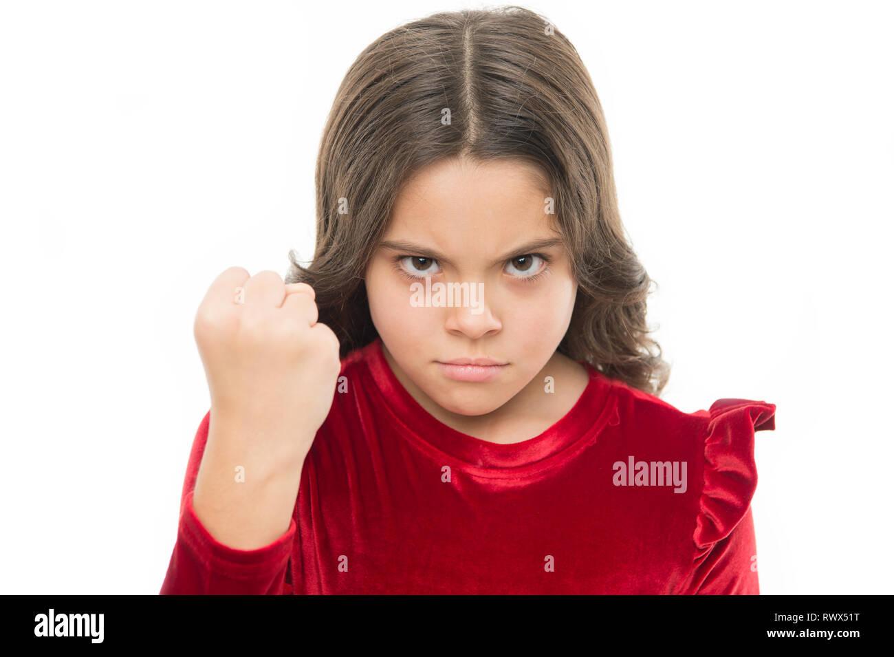 La menace de l'agression physique. Kids concept d'agression. Fille agressive menace de vous battre. Fille dangereuse. Vous êtes averti. Kid fille menaçant avec fist isolé sur blanc. Strong temper. Photo Stock