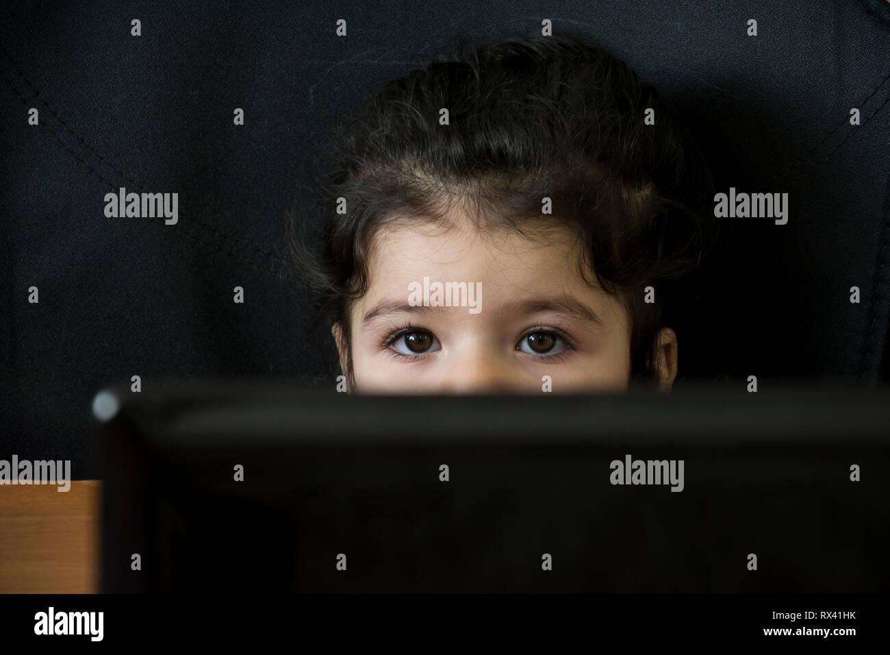 Portrait d'une petite fille inquiète derrière un ordinateur portable, formation informatique pour les enfants, la technologie concept curiosité Photo Stock