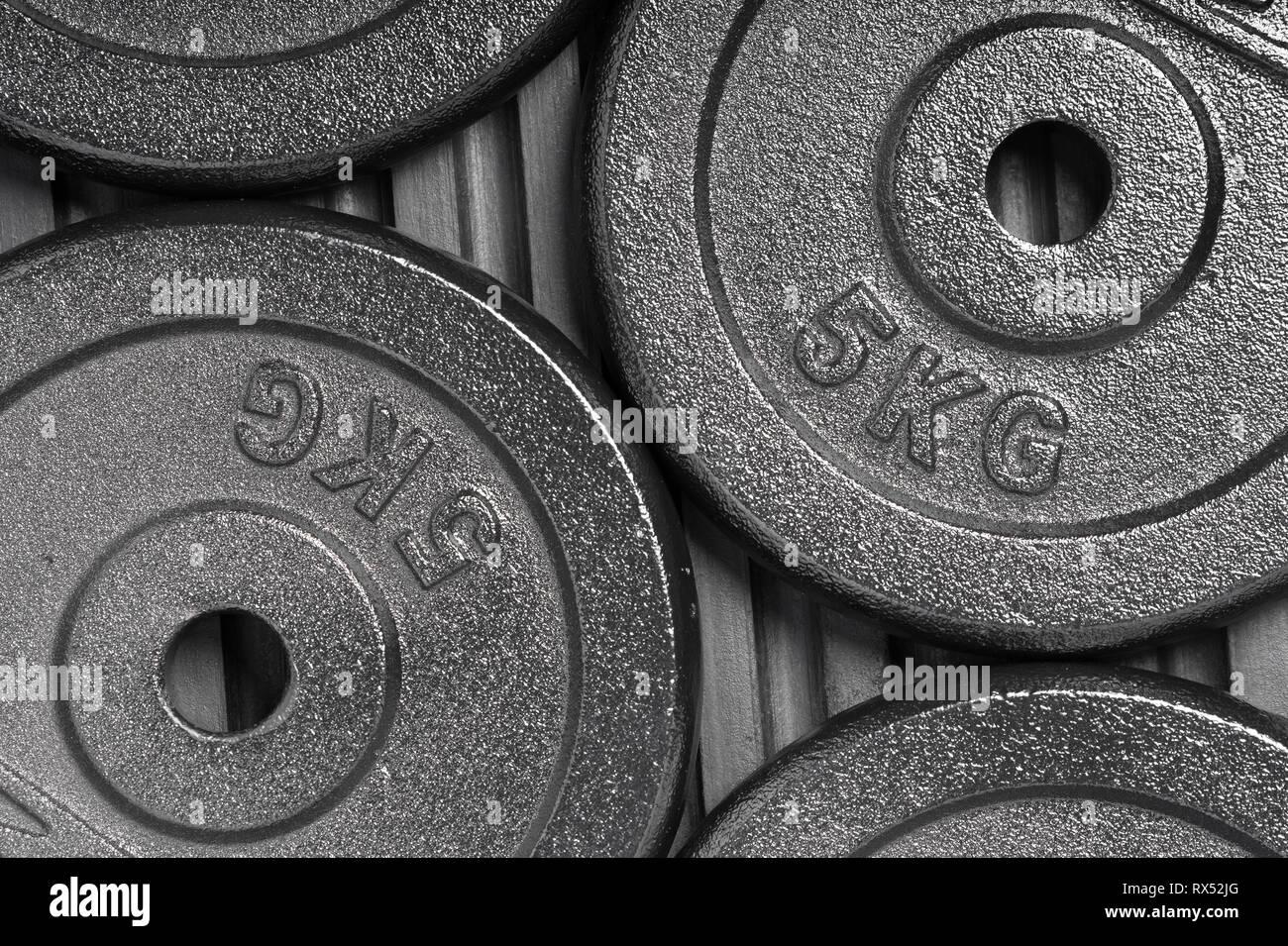 Les plaques de poids sur un sol en caoutchouc noir à l'intérieur d'une formation de poids salle de sport / fitness studio Photo Stock