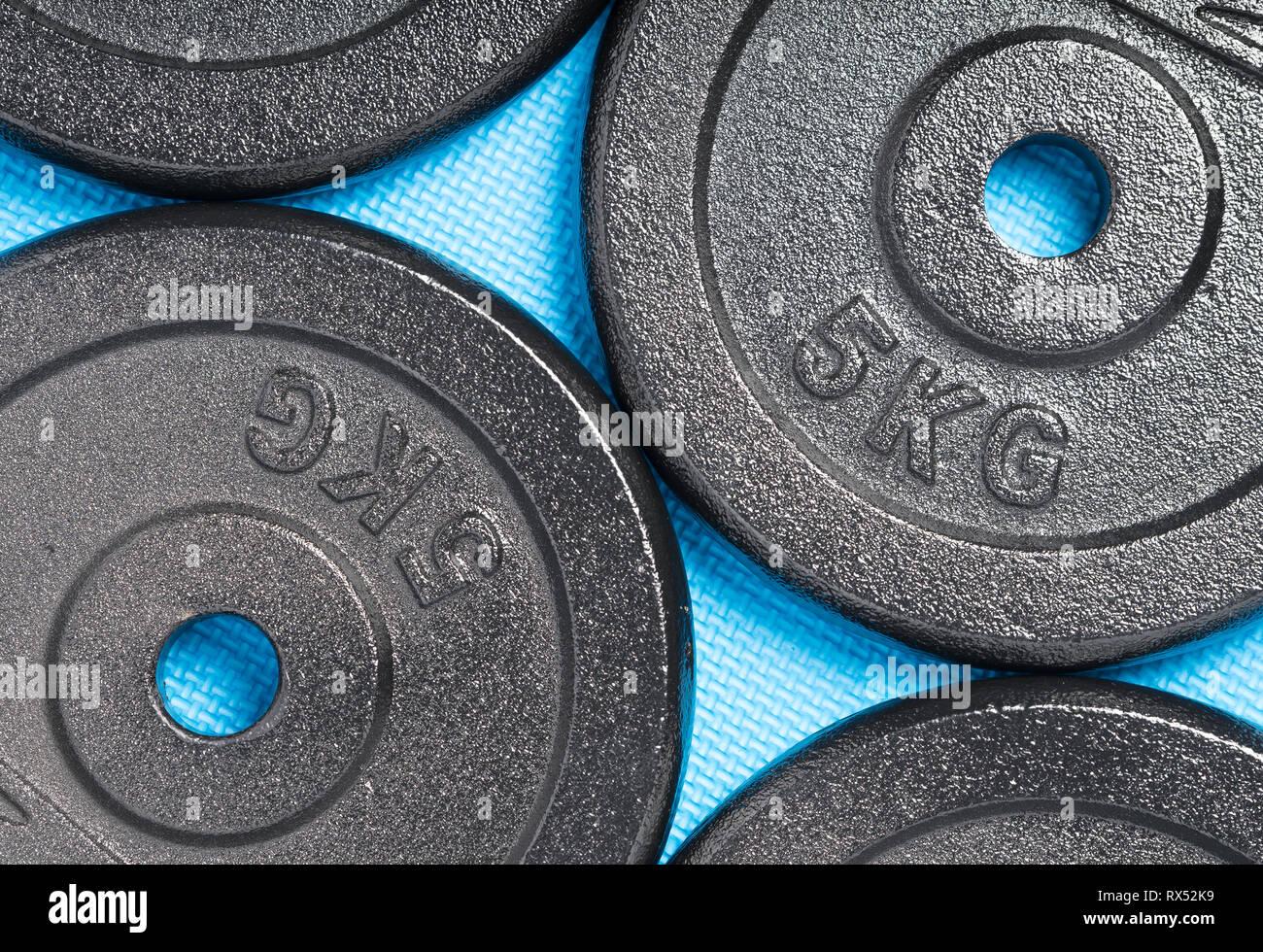 Les plaques de poids sur un sol bleu coloré à l'intérieur d'une formation de poids salle de sport / fitness studio Photo Stock