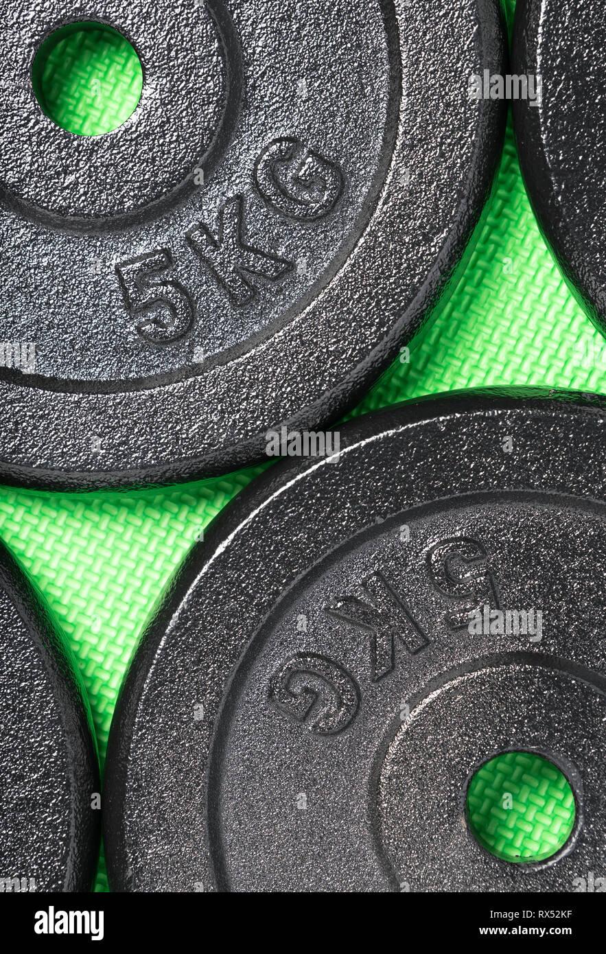 Exercice d'haltères sur un marbre vert à l'intérieur d'une salle de sport de formation de poids Photo Stock