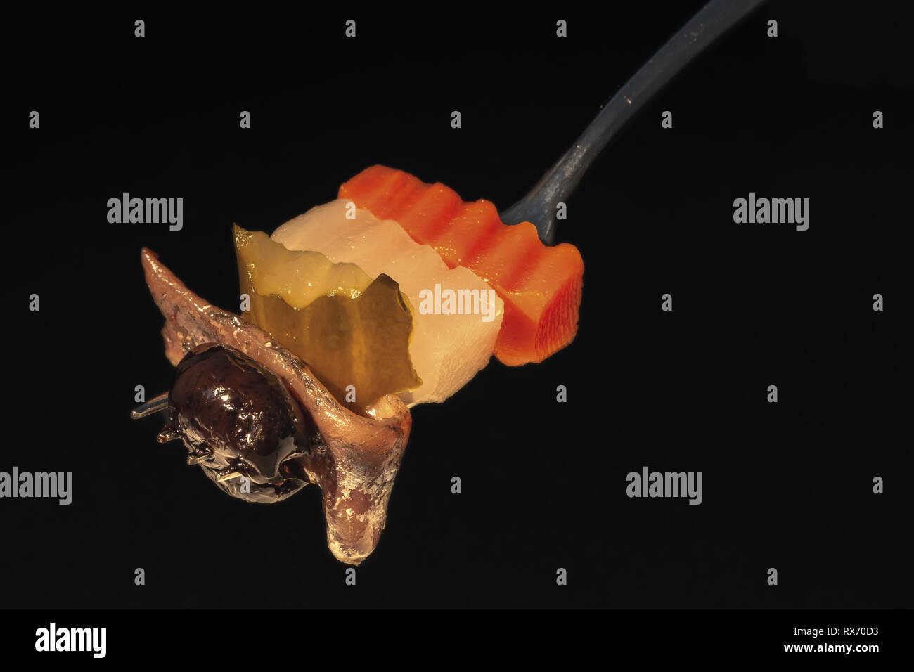 Forchetta con acciuga carota sedano bianco cetriolo Oliva Nera fondo nero da sopra Photo Stock