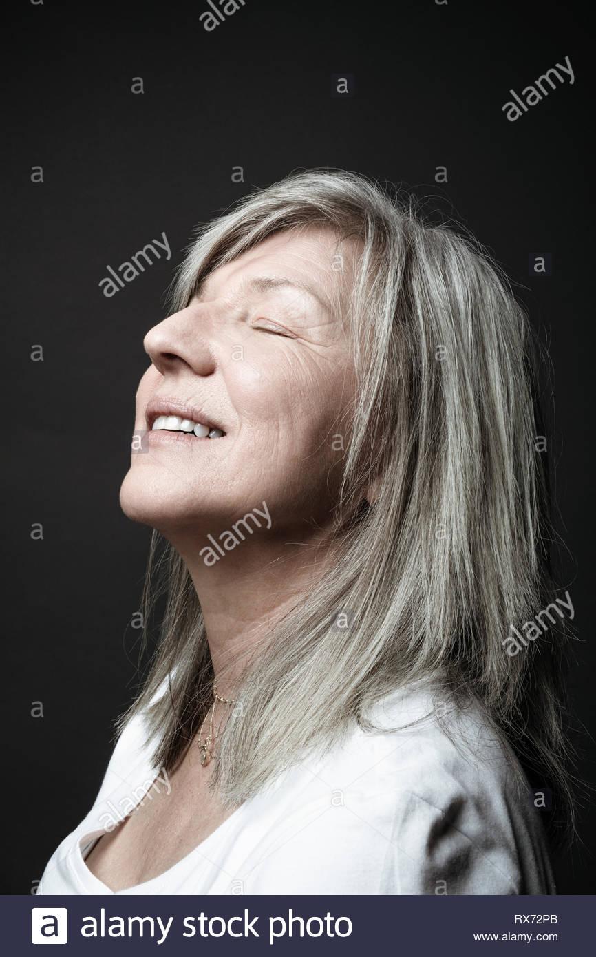 Belle femme sereine Portrait senior avec les cheveux gris et les yeux fermés, la tête en arrière Photo Stock