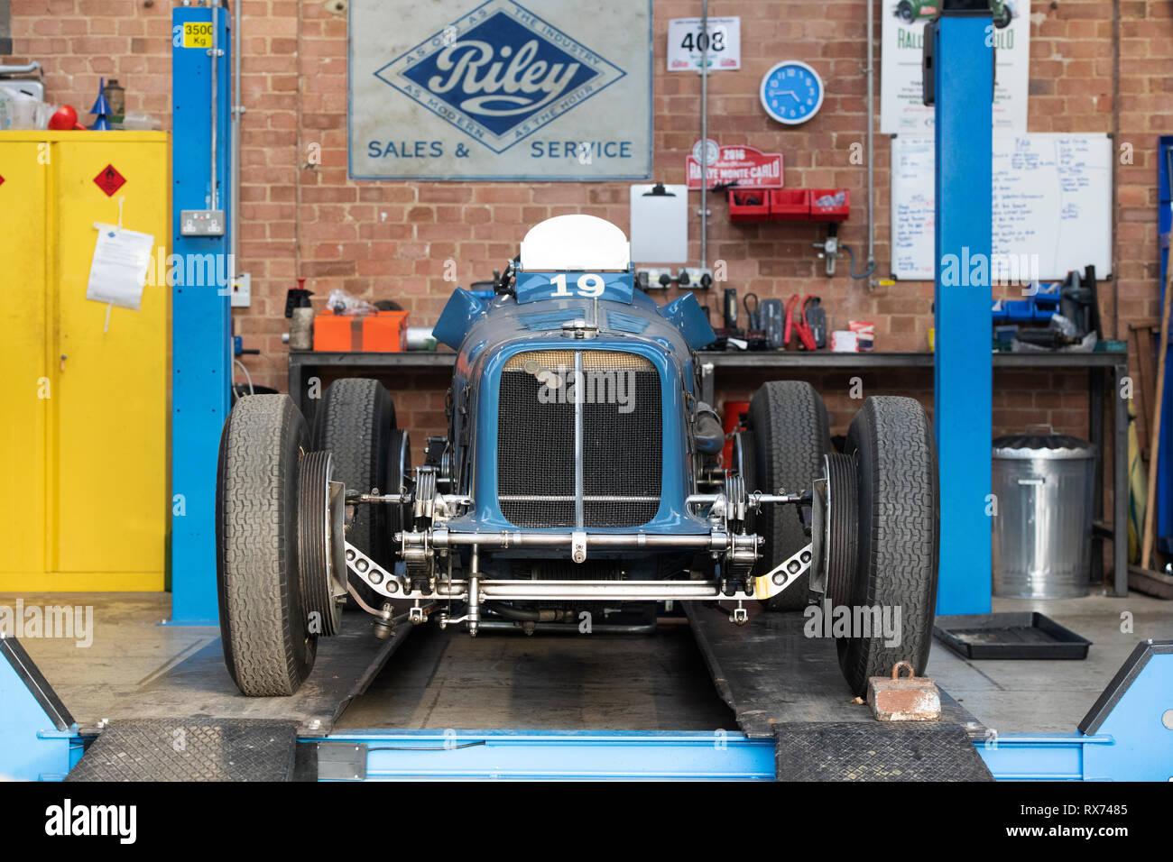 Ère Vintage (Français) Location de voitures de course sur une voiture ascenseur à l'intérieur d'un atelier de restauration vintage à Bicester heritage centre, Oxfordshire, Angleterre Photo Stock