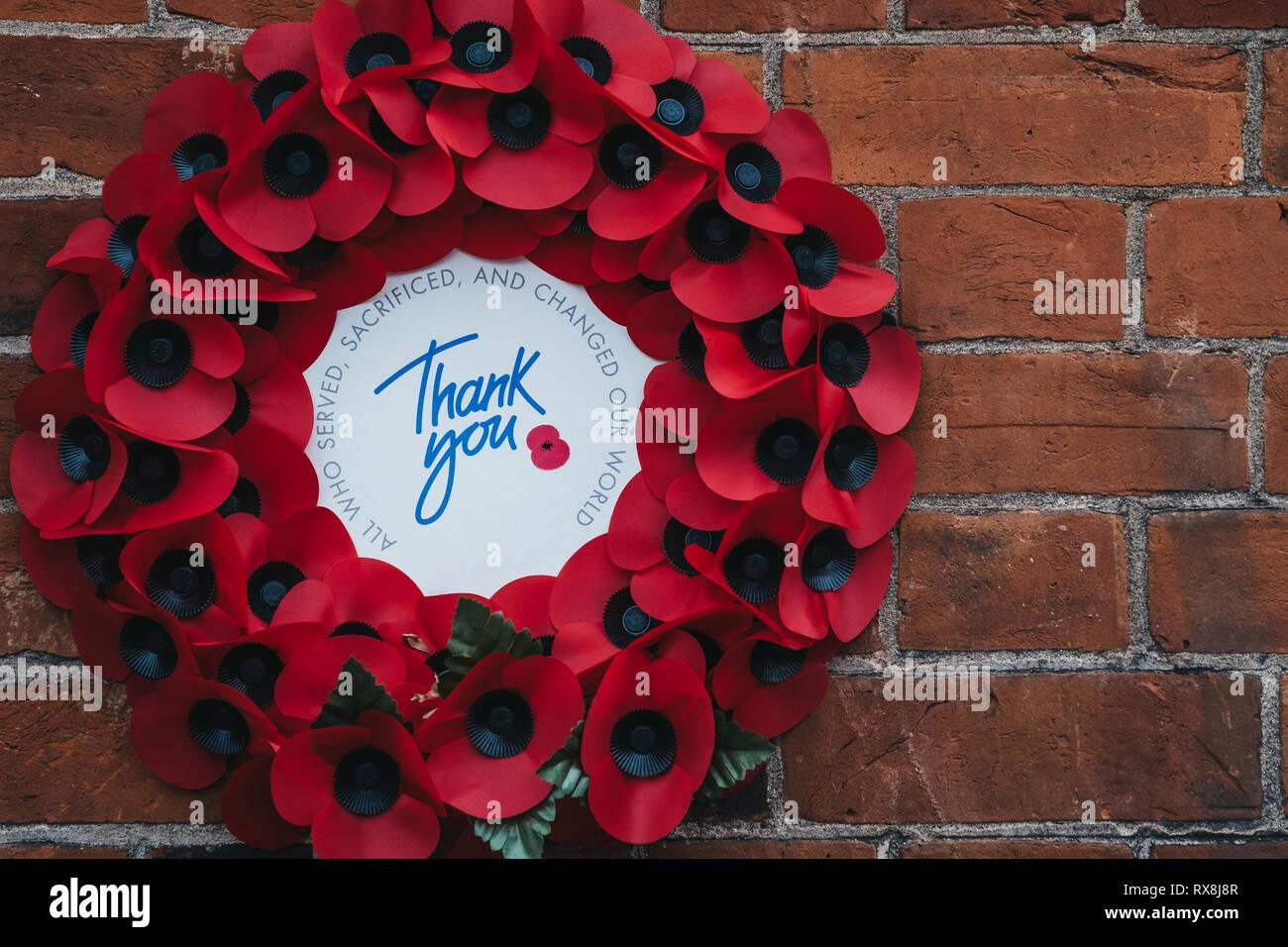 """Souvenir coquelicot rouge couronne, avec un """"Merci"""" message à l'intérieur sur un mur de briques. Photo Stock"""