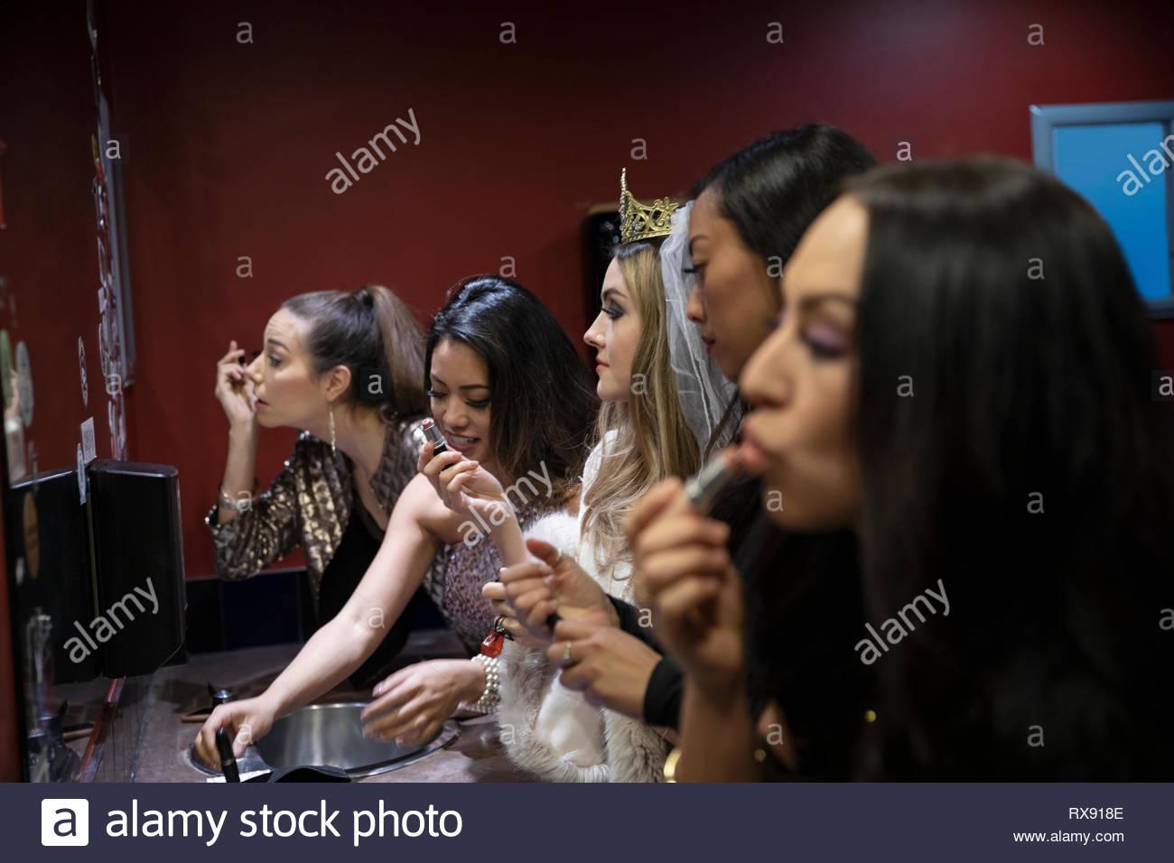 Et les amis de bachelorette appliquant le maquillage en boite miroir de salle de bains Photo Stock