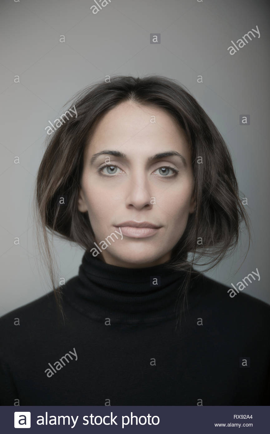 Portrait confiant belle jeune femme brune aux yeux bleus Photo Stock