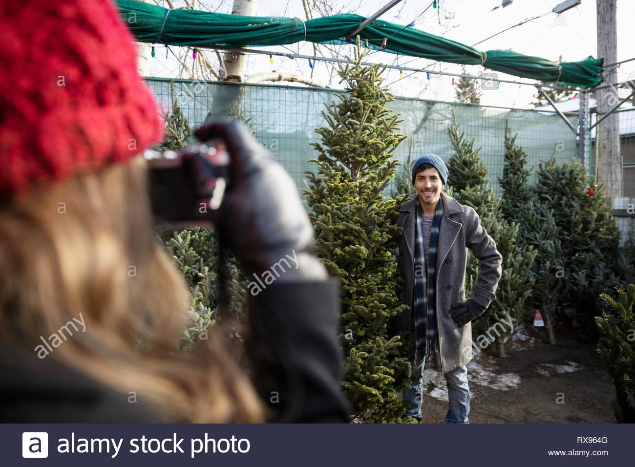 Femme avec caméra photographiant copain holding arbre de Noël Marché de Noël Photo Stock