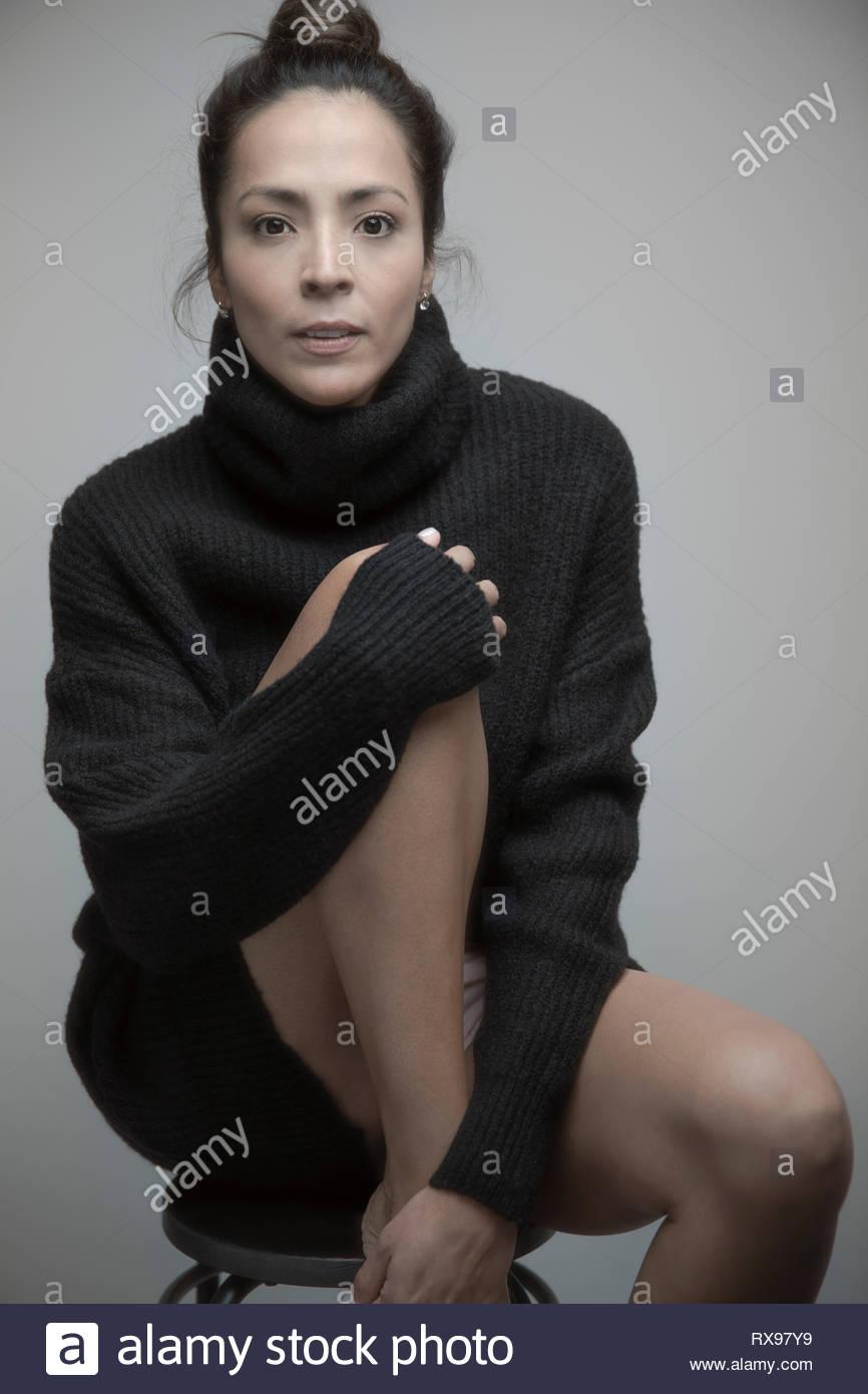 Portrait confiant belle Latina woman wearing sweater dress Banque D'Images