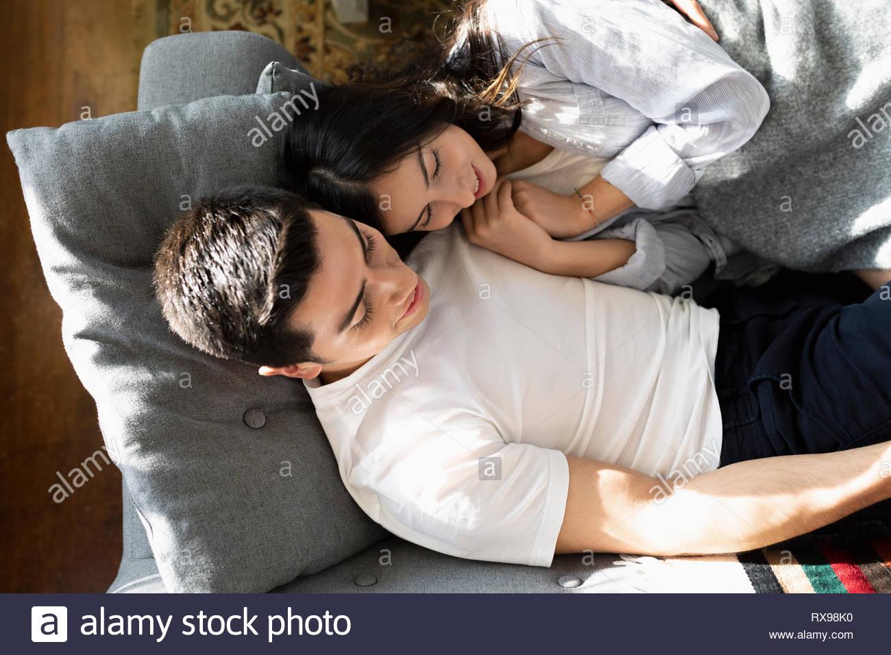 Vue de dessus young couple Latinx câlins sur canapé Photo Stock