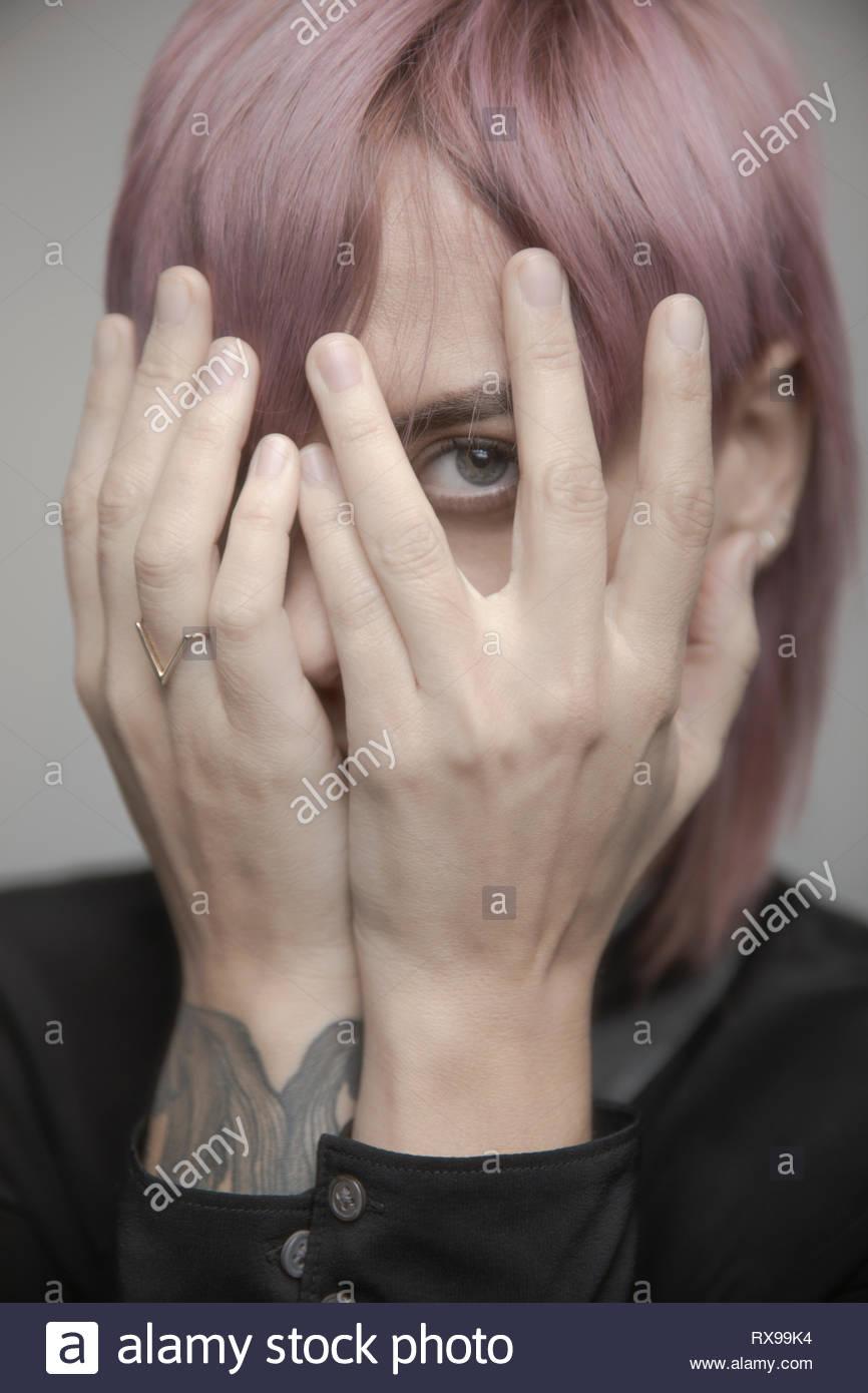 Magnifique Portrait de genre non-personne aux cheveux roses se cachant la tête dans les mains Photo Stock