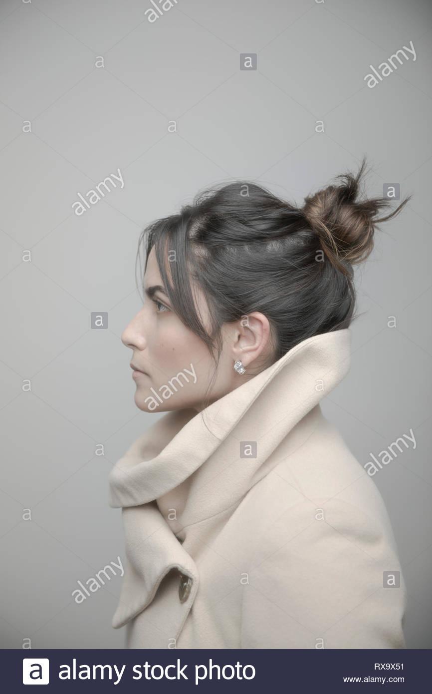 Portrait de profil belle jeune brunette Latina woman in coat looking away Photo Stock