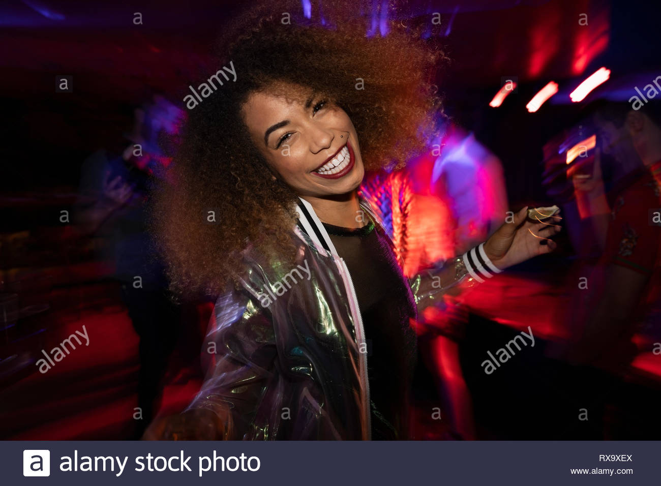 Carefree Portrait young woman dancing in nightclub Photo Stock