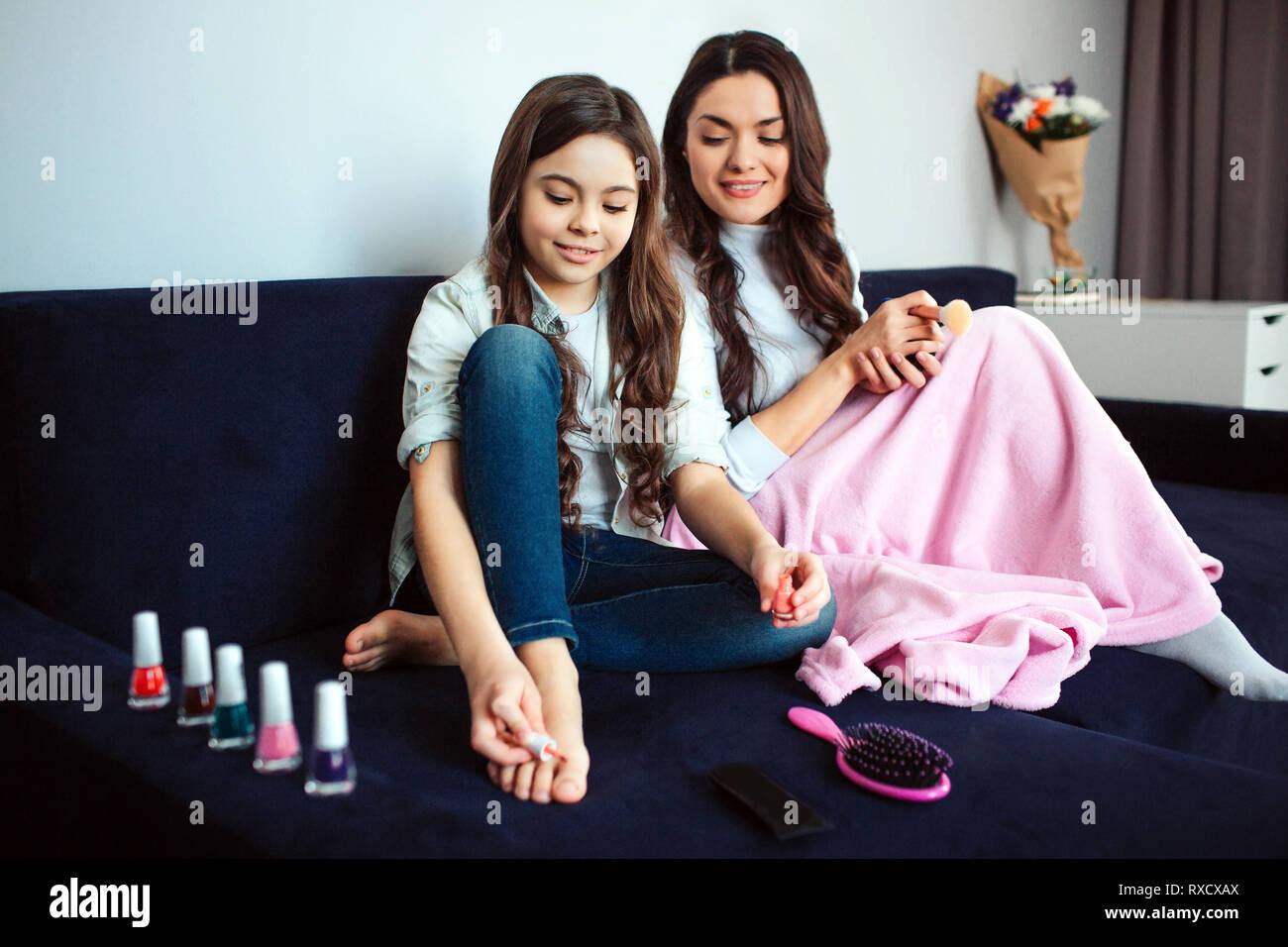 Belle brune portrait mère et fille s'asseoir ensemble dans la chambre. L'utilisation de vernis à ongles rose fille sur les orteils. Maman s'dowwn à elle et sourire. Ils s'asseoir Banque D'Images