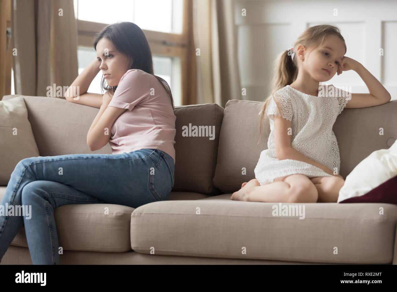 La mère et l'enfant têtu girl sitting refoulés sur canapé Banque D'Images