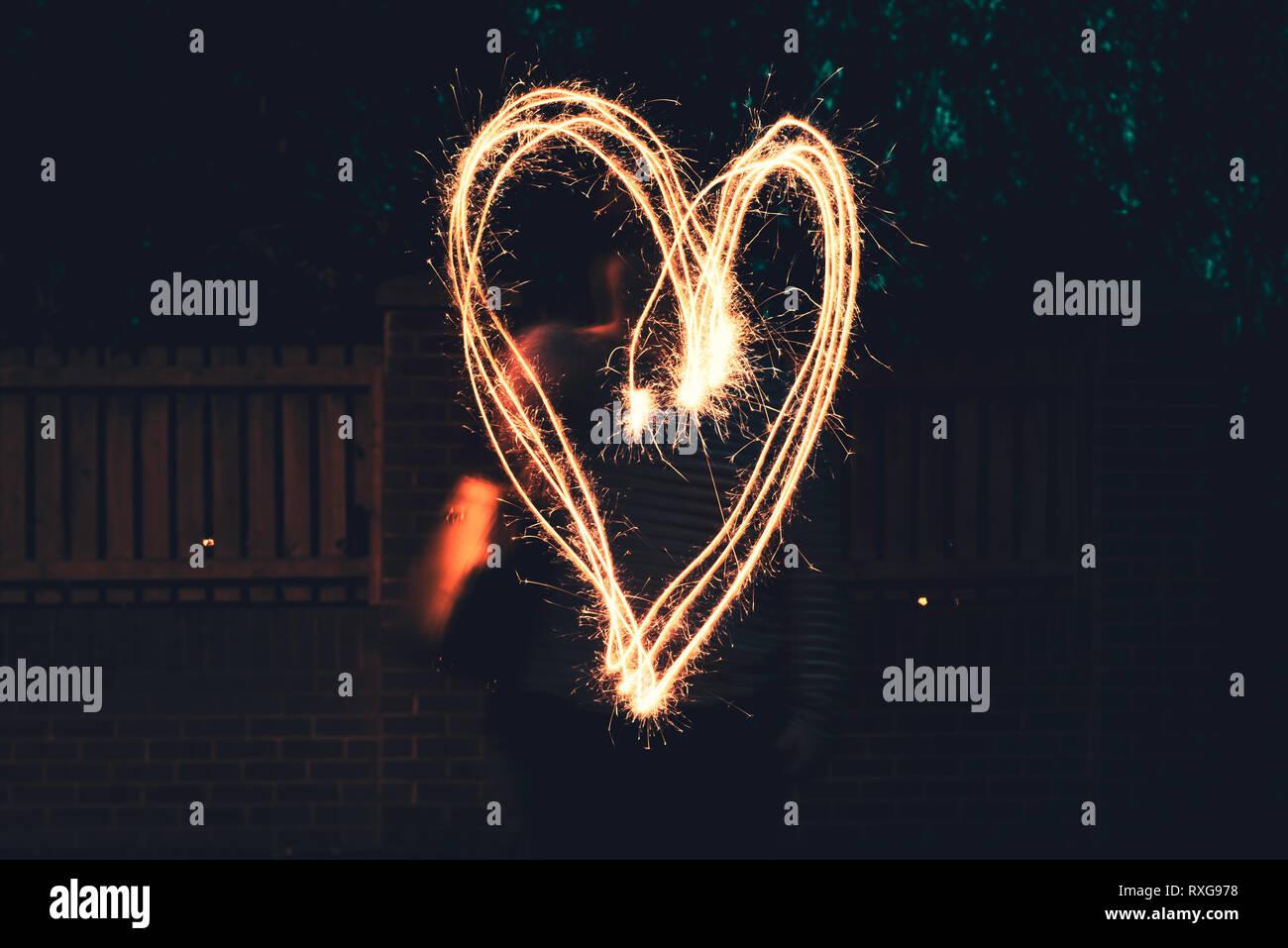 Un grand cœur dessiné à l'aide d'un cierge magique Banque D'Images