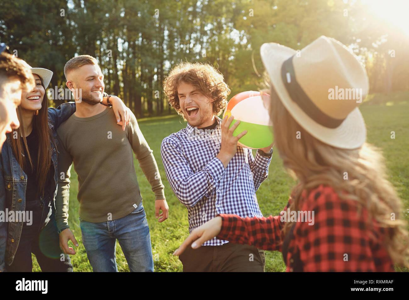 Les amis jouer dans le parc avec la balle dans l'été. Banque D'Images