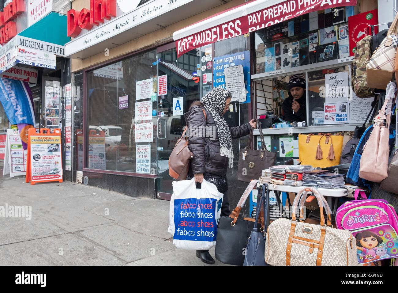 Une scène de rue à Jackson Heights, Queens, New York doté d''un couple de livres de poche à un stand en plein air sur la 74e Rue. Photo Stock