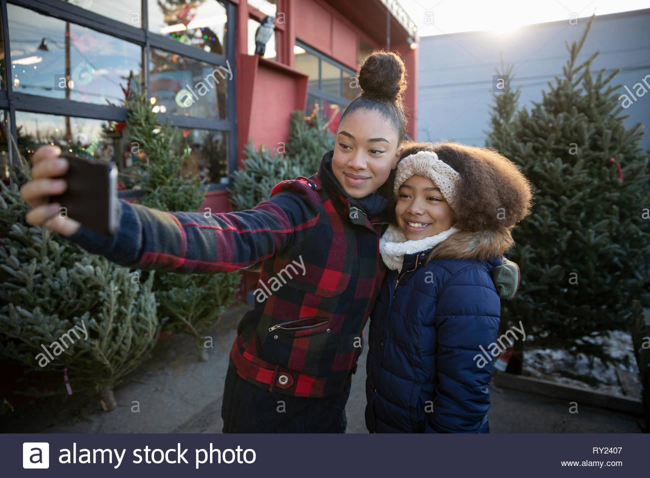 Les sœurs avec téléphone appareil photo en tenant au marché de l'arbre de Noël selfies Photo Stock