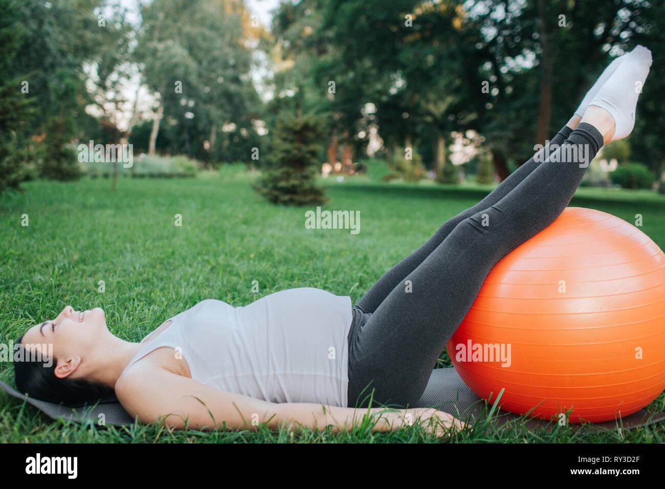 Nice young pregnant woman lying on yoga mat en parc. Elle tenir les jambes sur l'orange fitness ball et regardez vers le haut. S'étend du modèle et l'ensemble du corps. Photo Stock