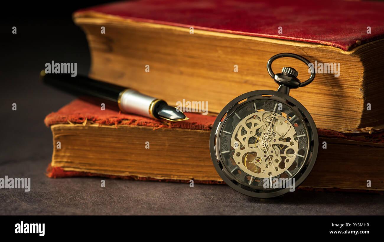 Montre de poche liquidation placée à côté du vieux livre et la plume sur le livre dans l'obscurité et la lumière du matin. Photo Stock
