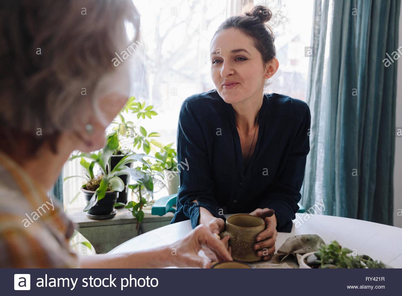 Fille heureux de boire du café avec la mère à table Photo Stock