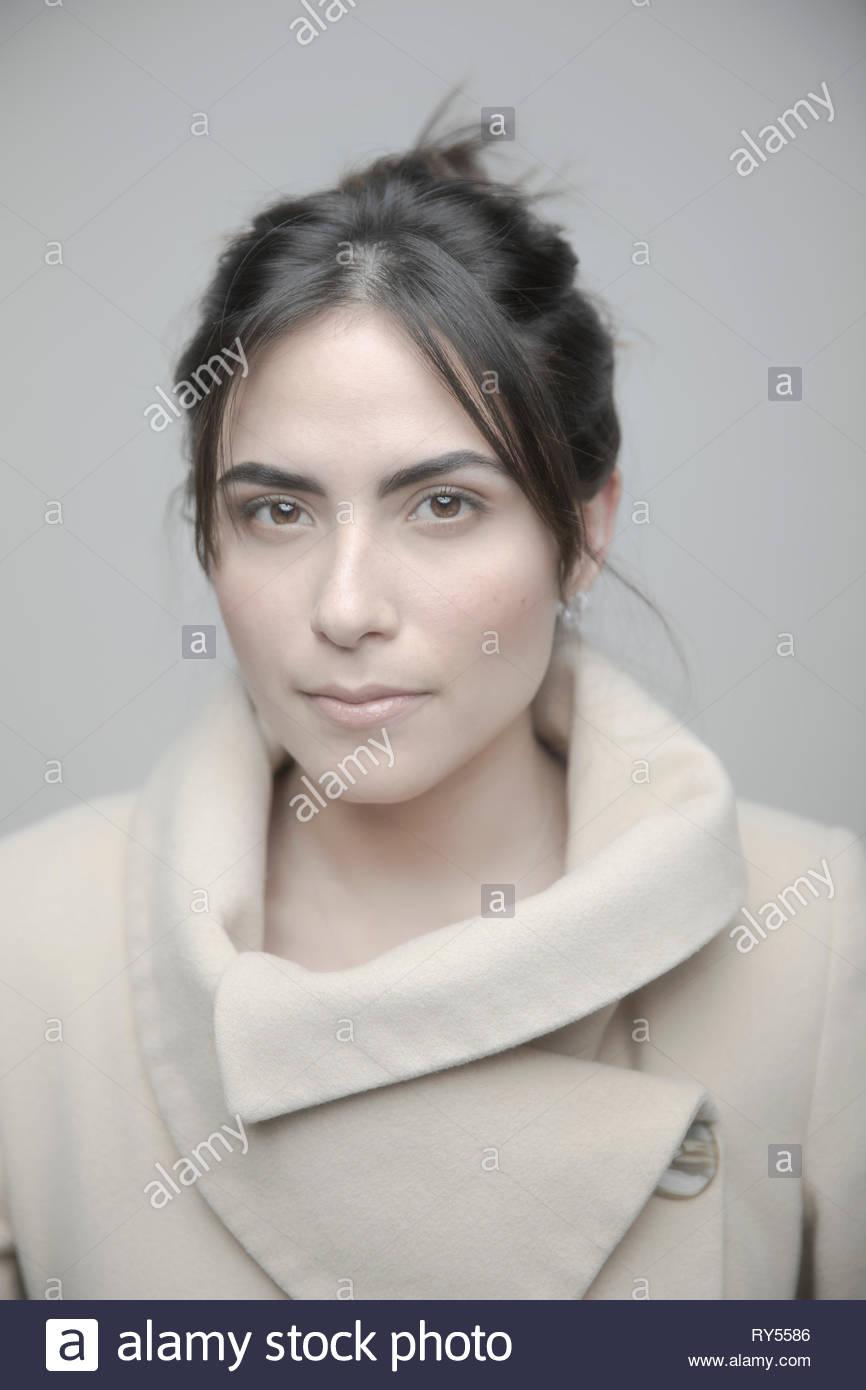 Portrait confiant belle jeune femme en manteau beige Photo Stock