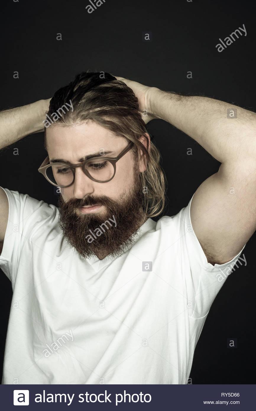Beau jeune homme hipster avec barbe et mains en tête Banque D'Images