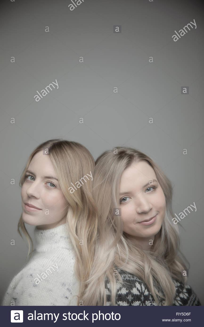 Portrait confiant belle jeune femme blonde standing back to back Photo Stock
