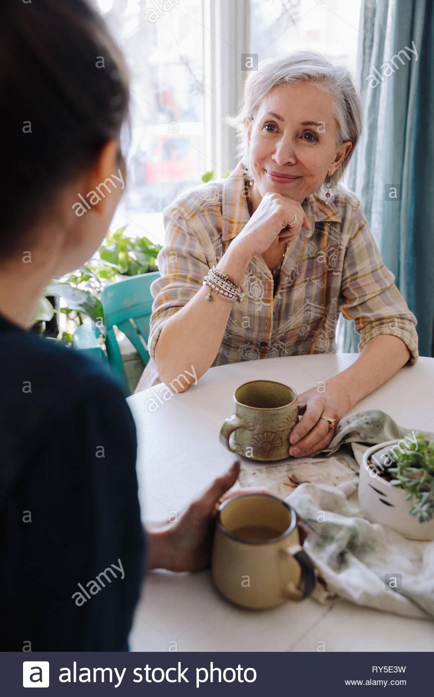 Mère et fille de parler, boire du thé Photo Stock