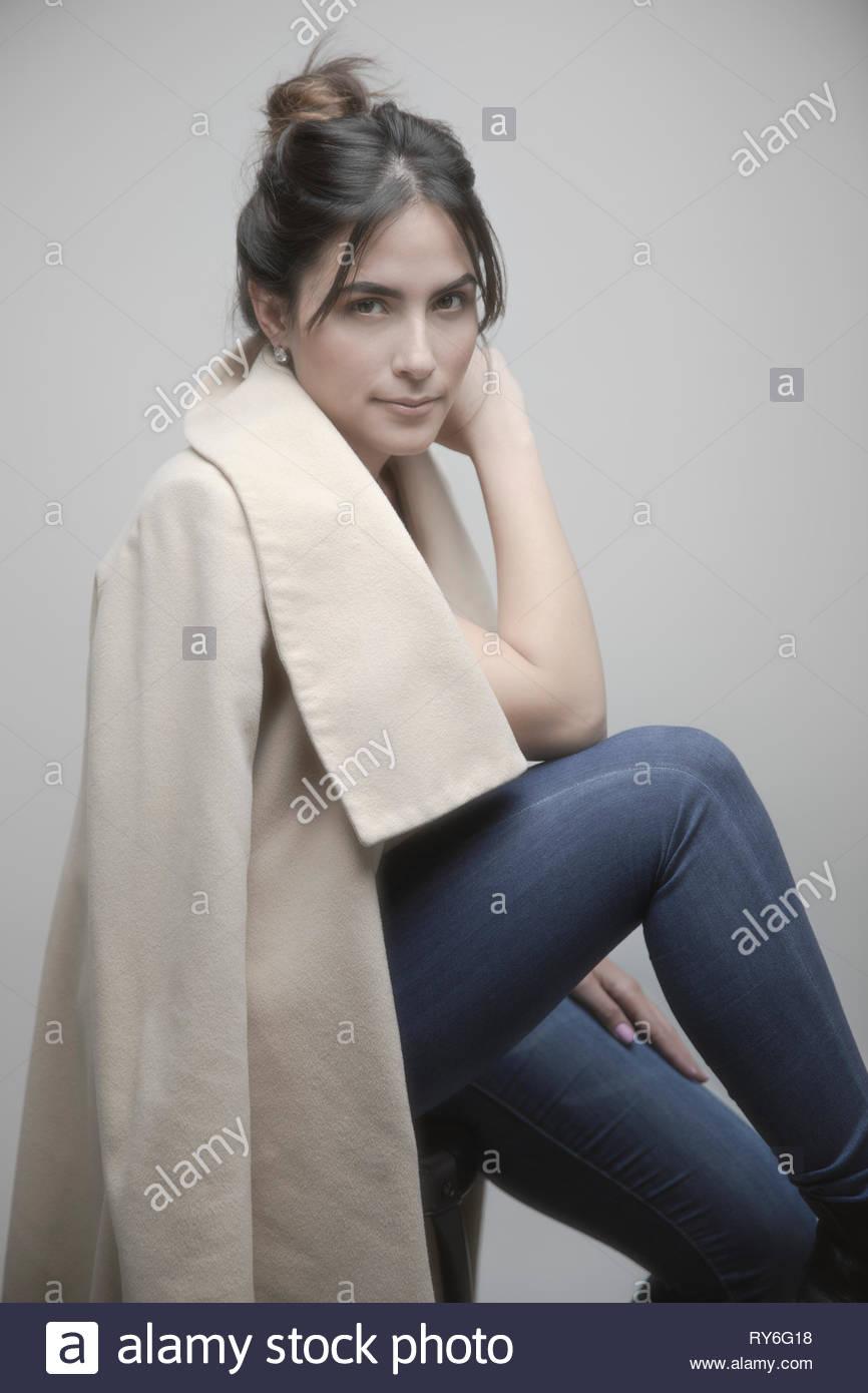 Portrait confiant belle jeune latina woman manteau beige Photo Stock