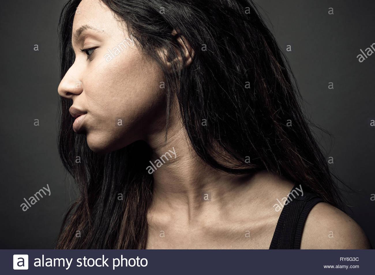 Portrait de profil belle jeune femme jamaïcaine réfléchie avec de longs cheveux noirs Photo Stock