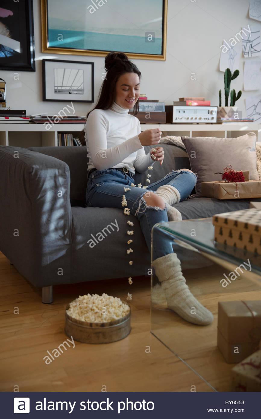 Jeune femme qui met des popcorn décoration de Noël dans la salle de séjour Photo Stock