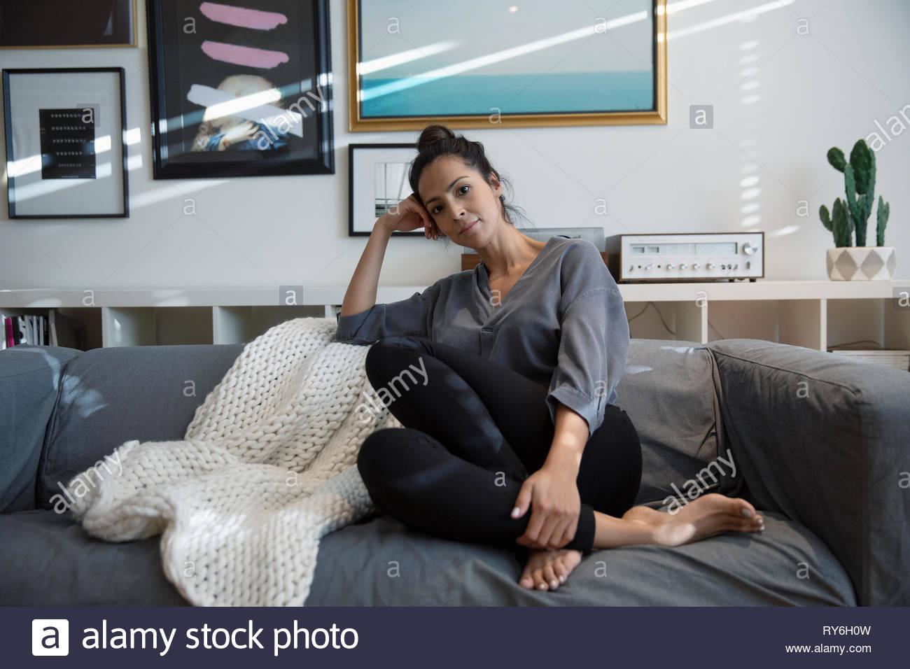 Portrait confiant Latina woman relaxing on sofa du salon Photo Stock