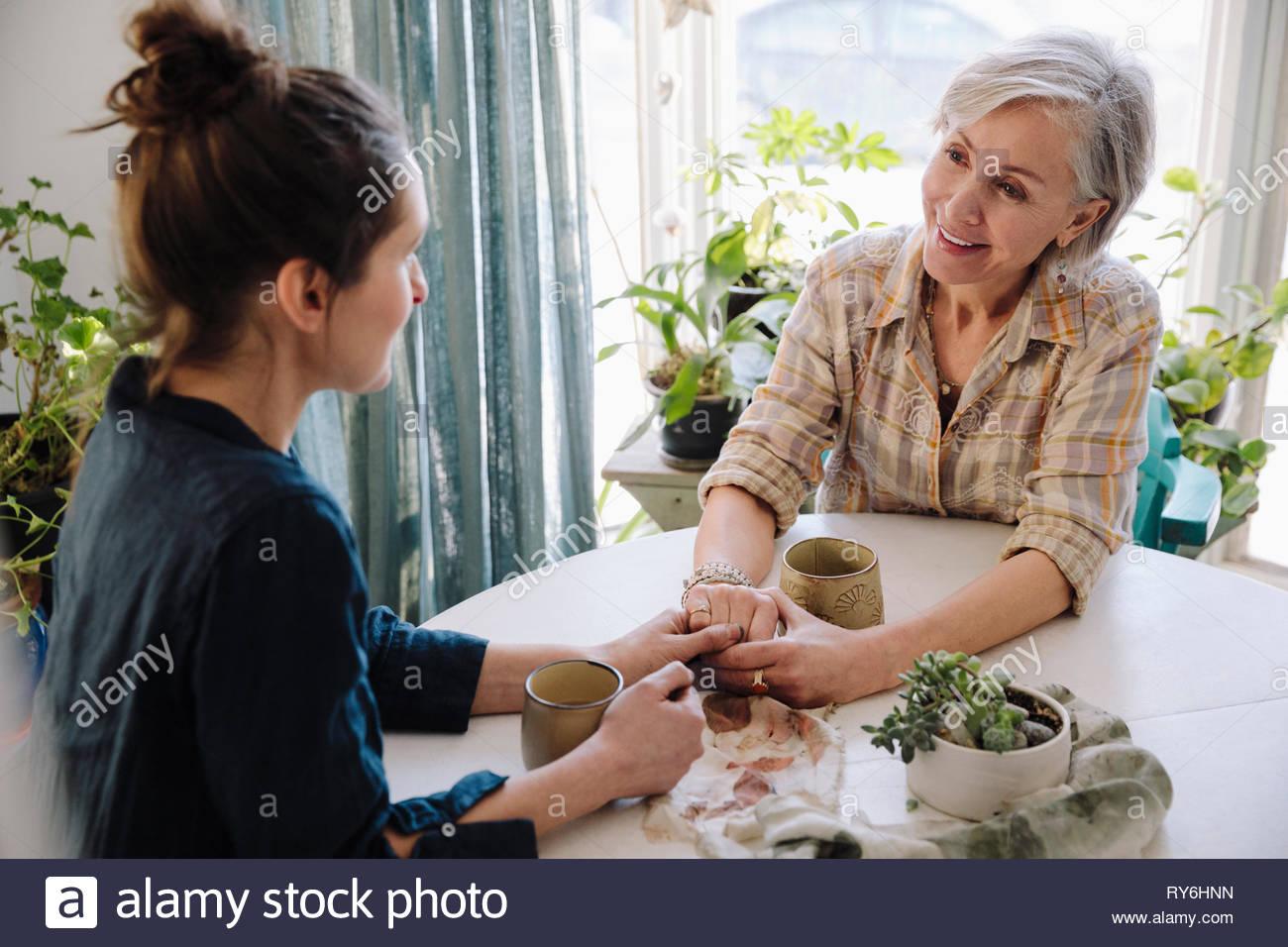 Mère et fille se tenant la main et de boire du café à table Photo Stock