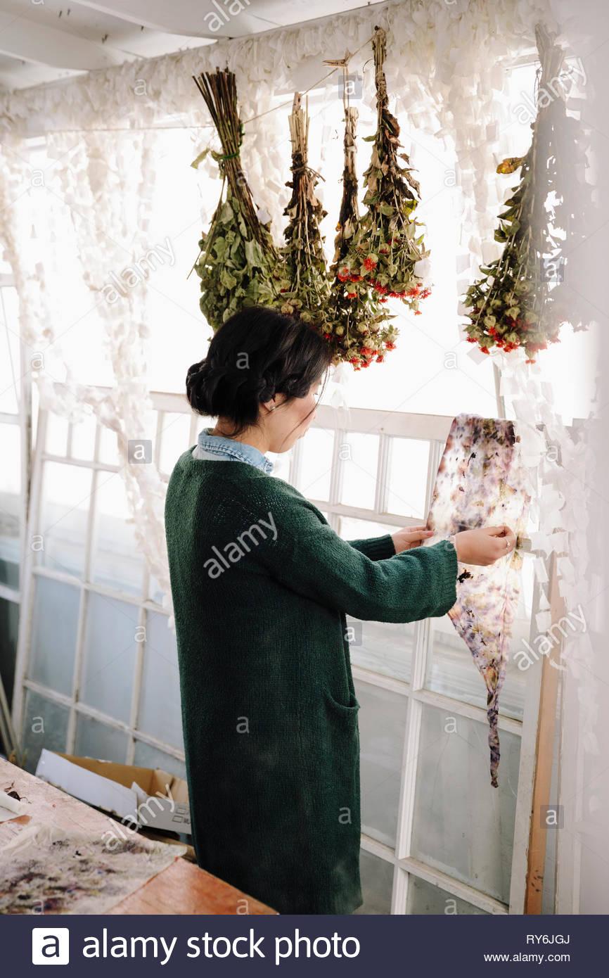 Artiste femme fleurs de séchage pour la fabrication du papier en studio Photo Stock