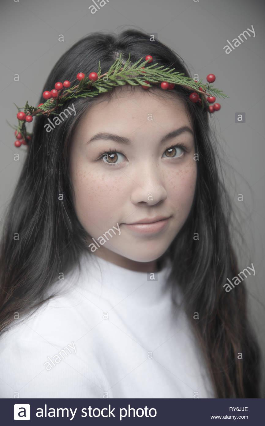 Portrait confiant belle brunette woman wearing christmas wreath on head Photo Stock