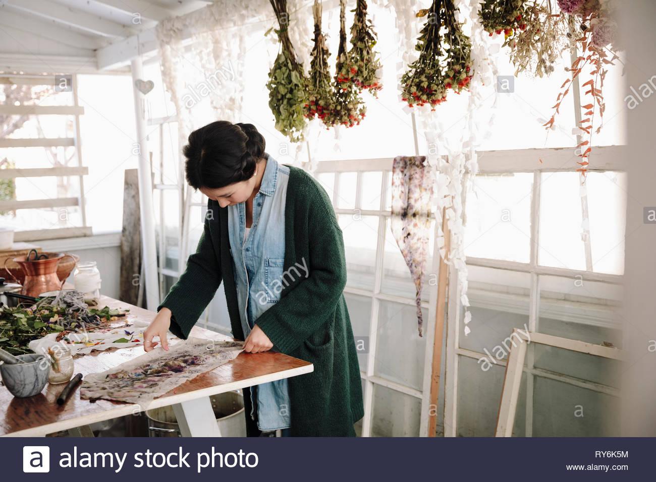 Femme appuyant sur les fleurs séchées pour la fabrication du papier Photo Stock