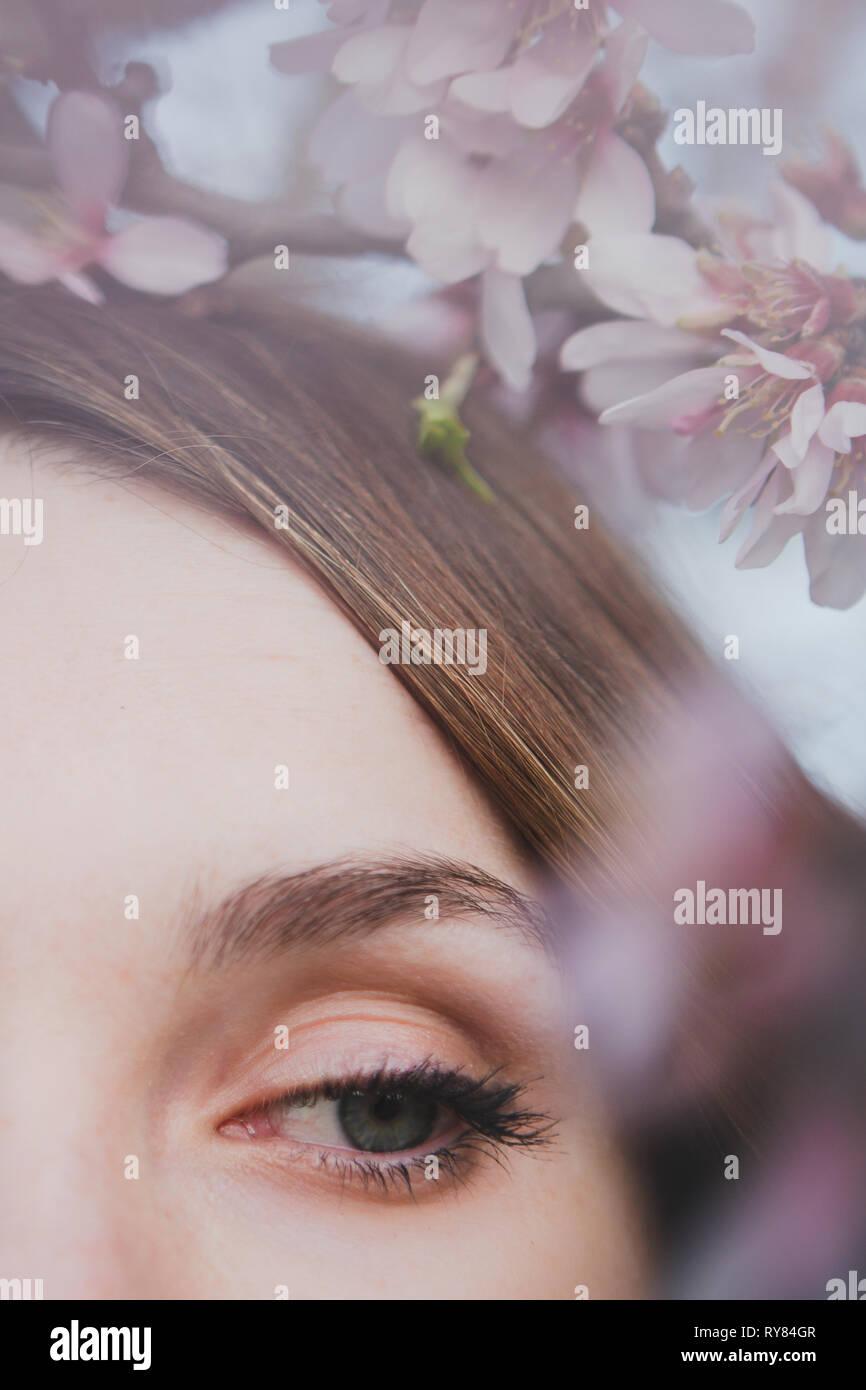 Petit visage de jeune fille aux yeux bleus près de branche de bois en fleurs Banque D'Images