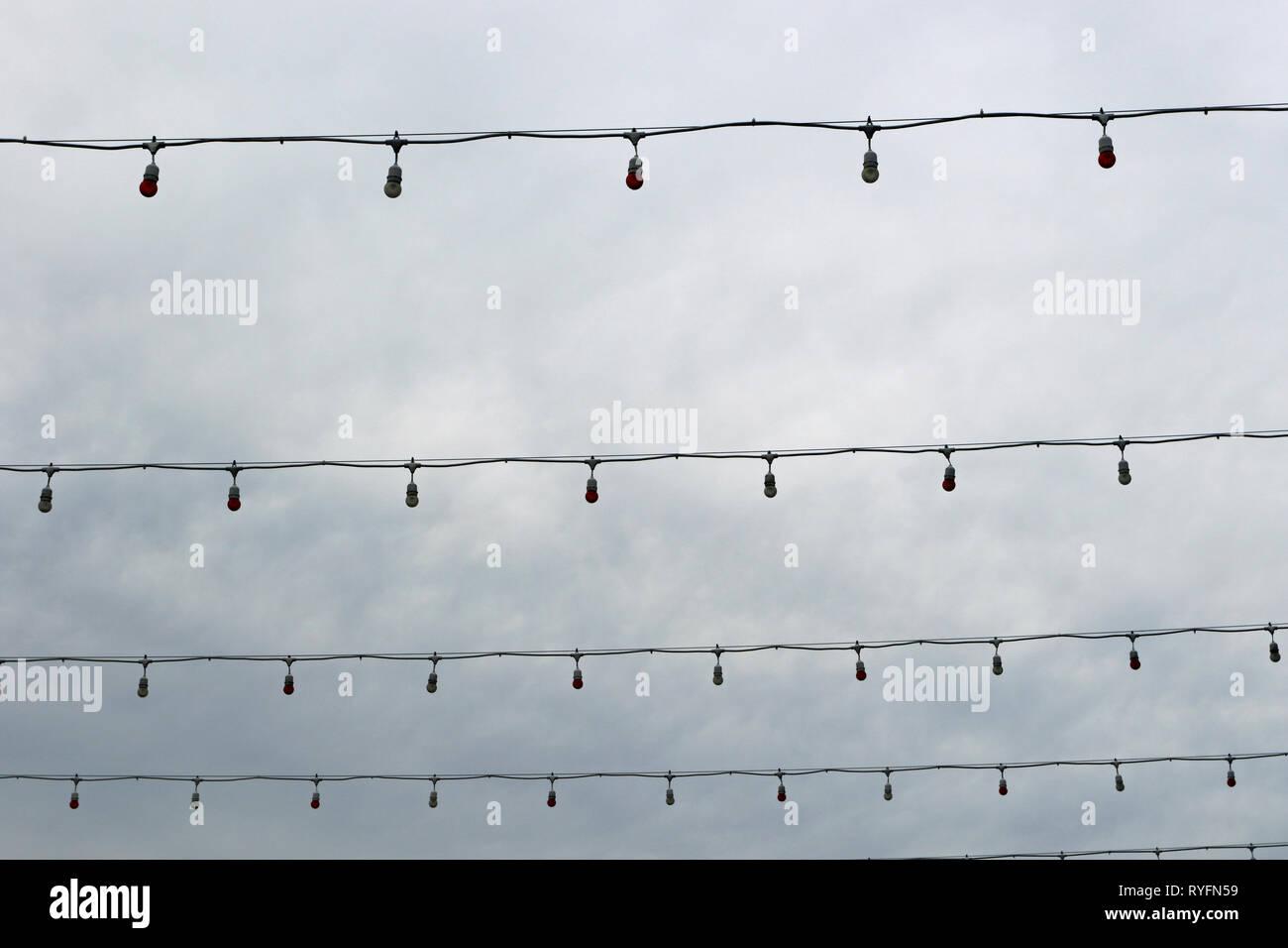 Pas d'éclairage cordes des lumières enfilés sur une rue sur une morne journée. Photo Stock