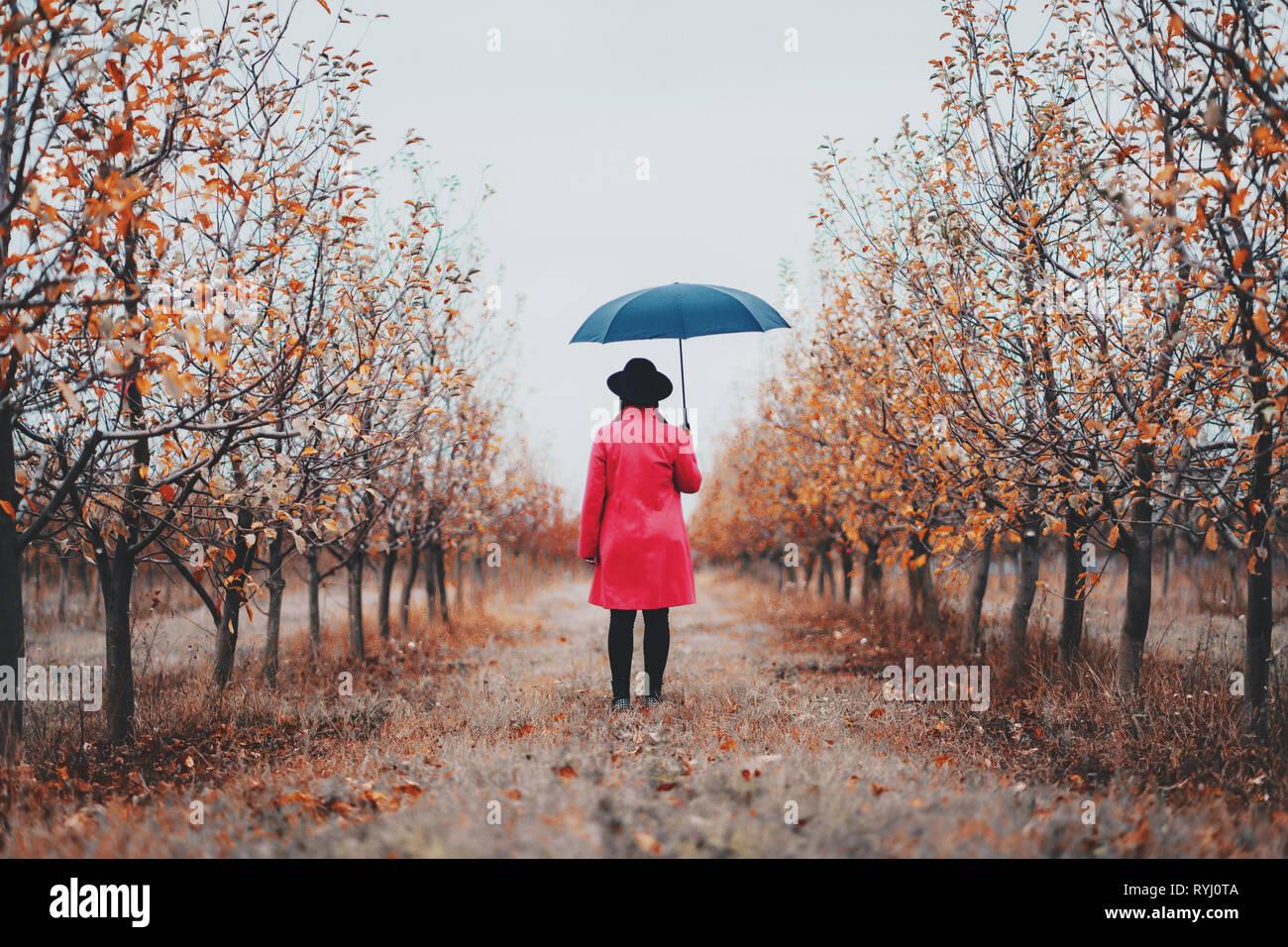 Femme en robe rouge et avec parapluie entre les arbres dans le jardin d'Apple à l'automne. Le minimalisme, voyages, nature concept. Banque D'Images