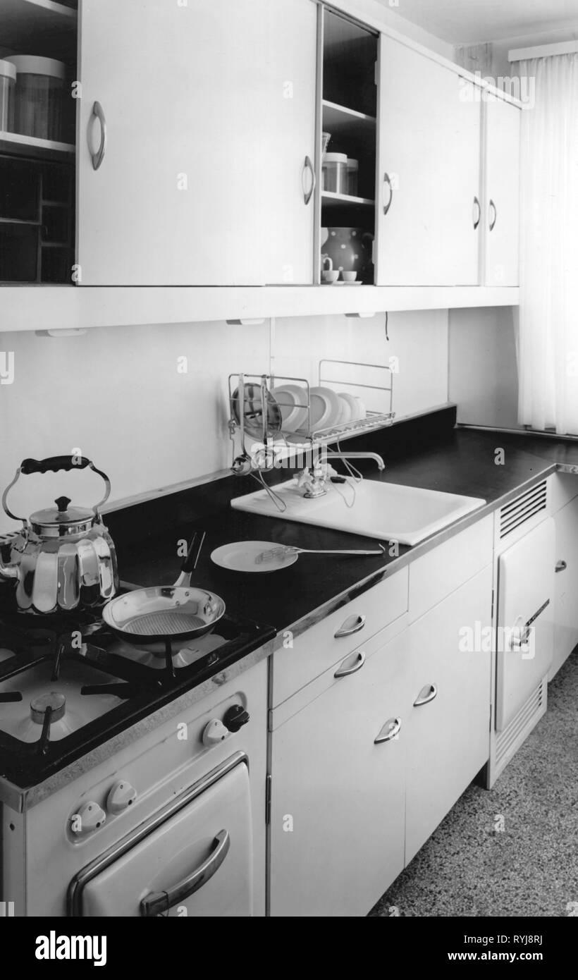 Ménage, cuisine et ustensiles de cuisine, cuisine, 1950, objet, objets, photos, appareil de cuisine, cuisine, ustensiles de cuisine, four, micro-ondes, le stockage, cuisinier, la cuisine, la cuisson, la cuisson au four, meubles de cuisine, évier de cuisine, les éviers de cuisine, cuisine, cuisinière, cuisinière à gaz, les fours à gaz, poêle, friteuse, poêle, poêles, poêlons, cocotte, casserole à ragoût, cocottes, poêles à ragoût, bouilloire, théière, bouilloires, électrique, bouilloires, placards, placard mural, vaisselle, lave vaisselle, vaisselle, ménage, ménage, cuisine, cuisines, historique, historique, 20e siècle, Additional-Rights Clearance-Info-Not-Available- Photo Stock