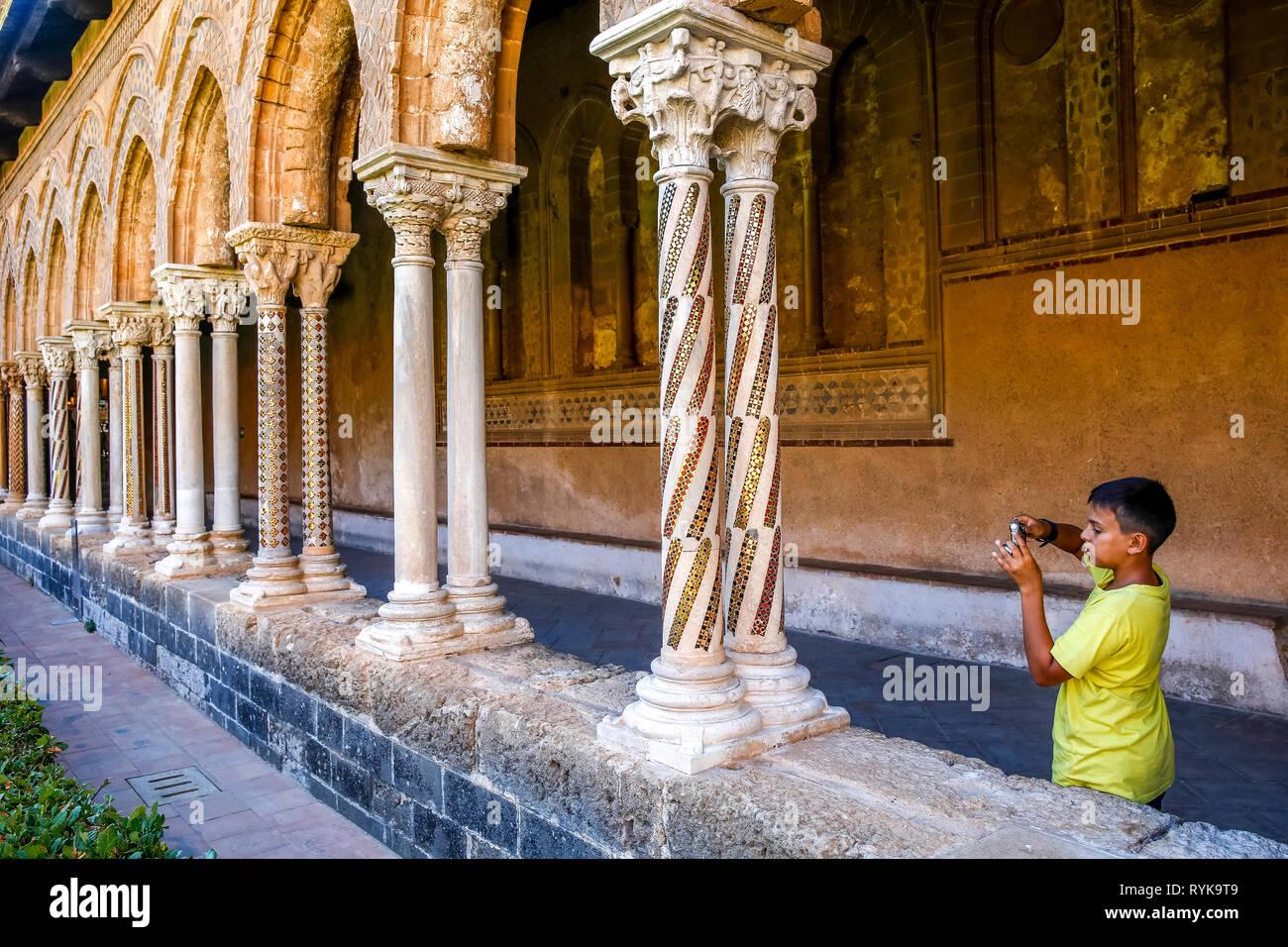 Jeune garçon de 12 ans de prendre une photo dans le cloître de la cathédrale de Monreale, Sicile (Italie). Photo Stock