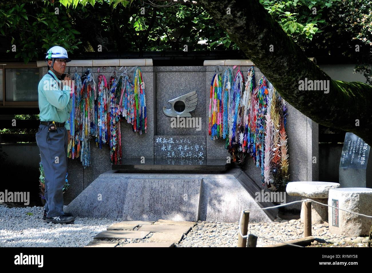 Parc Ueno, TOKYO, JAPON - Juillet 9, 2018: un travailleur debout à côté de la CND Peace monument à Ueno Park, tandis que le jeûne son casque à Tokyo au Japon Photo Stock