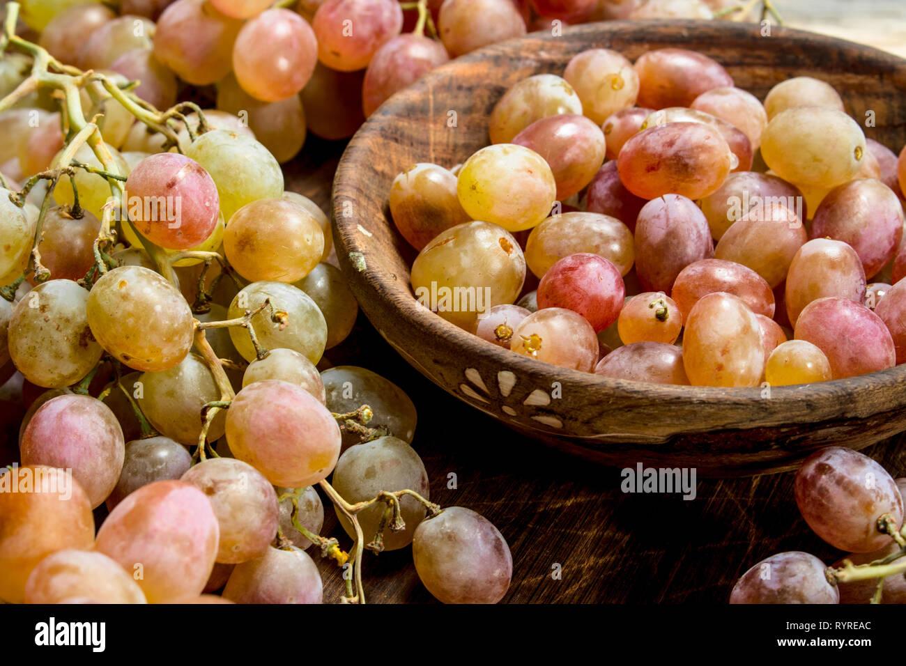 Les raisins dans un bol rose . Sur un fond de bois. Banque D'Images