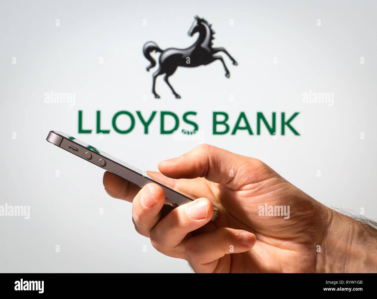 Un homme à l'aide de la Banque Lloyds Banking en ligne sur son téléphone portable Photo Stock