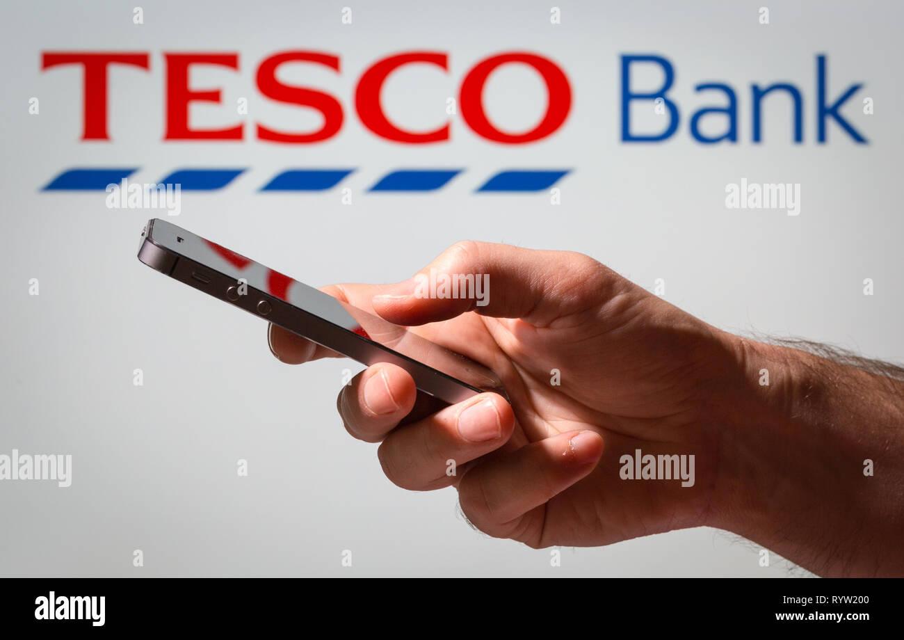 Un homme à l'aide des services bancaires en ligne Banque Tesco sur son téléphone mobile Photo Stock